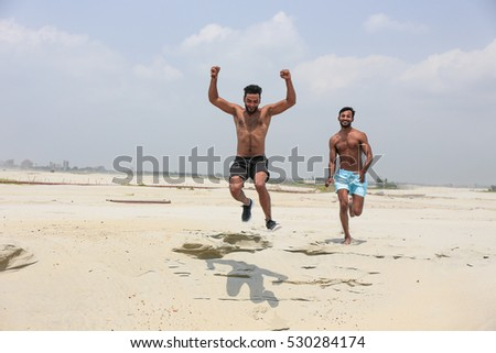 Two muscled fitness models jumping at the yellow beach