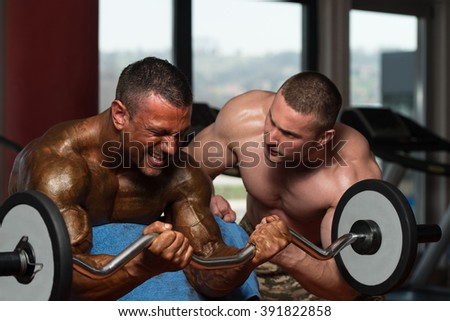 Two Muscular Men Doing Heavy Weight Exercise For Biceps In Gym - stock photo