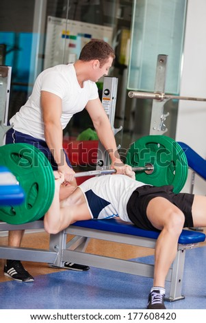 Two muscular young man working out in the gym
