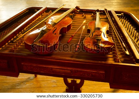 two music string instrument  in gold light on cimbalom - stock photo