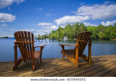 Two Muskoka Chairs Sitting On A Wood Dock Facing A Calm Lake. Across The  Water