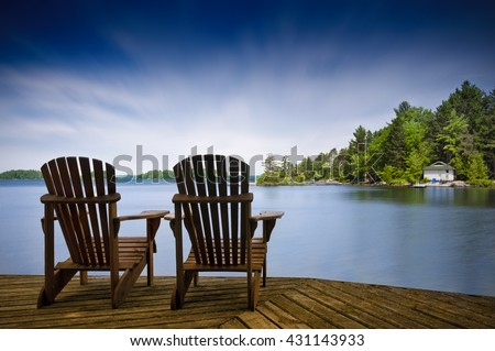 Two Muskoka Chairs Sitting On A Wood Dock Facing A Lake. Across The Calm  Water