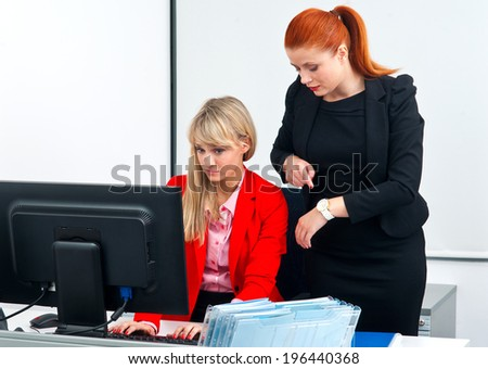 two nervous woman colleague workers in office working on deadline in computer - stock photo