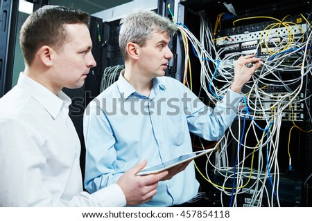 two network support engineers administrating in server room - stock photo