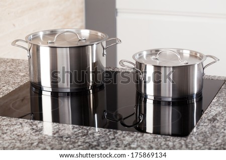 Two new metal pots in the kitchen on induction hob - stock photo