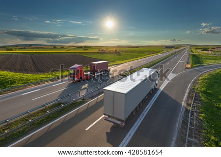 Two new modern trucks driving towards the sun at idyllic sunny day. Fast blurred motion drive on the freeway. Freight scene on the motorway near Belgrade, Serbia. - stock photo