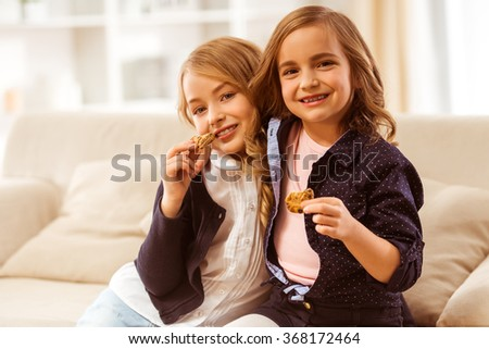 Two nice girls sitting on white sofa at home and cookies keep in the hands