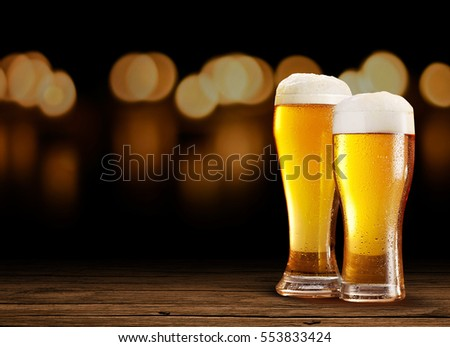 Two Nice Glasses of Beer in right on the wooden rustic table with black and bokeh effect background at night, on a dark pub.