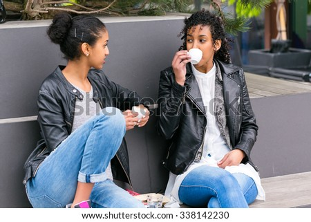 Two north African teen friends drinking together coffee outside  - stock photo