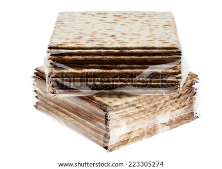 Two nylon wrapped packages of Jewish Matzah bread, the substitute for bread on the Jewish Passover holiday, isolated on white background. - stock photo