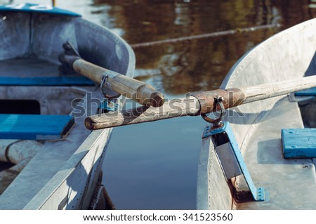 Two oar handles crossing, rowboats at a boat station - stock photo