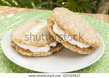 Two oatmeal cookie ice cream sandwiches served outdoors