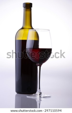 Two objects of green filled bottle and glass goblet with red dessert wine standing near each other isolated on grey white studio background with nobody, vertical picture - stock photo
