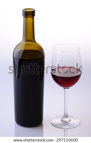 Two objects of green full bottle and glass bocal with red dessert wine standing near each other isolated on grey white studio background, vertical picture - stock photo