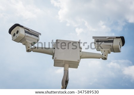 two of CCTV security camera with blue sky - stock photo