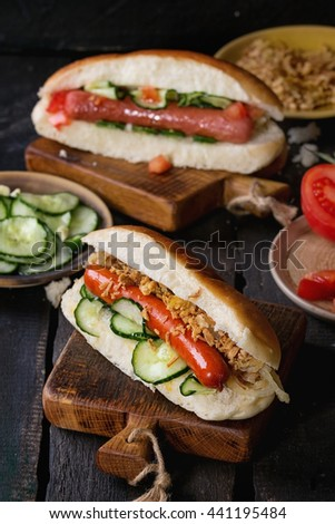 Two of homemade hot dogs with sausage, fried onion, tomatoes and cucumber, served with ingredients in different plates on wood chopping board over old wooden background. Rustic style. - stock photo