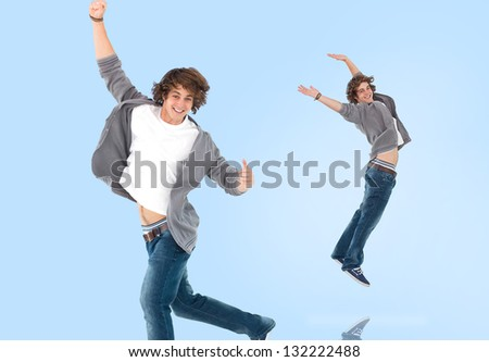 Two of the same teenage boy jumping for joy on blue background