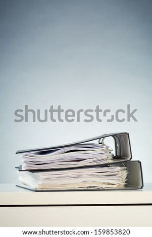 Two office binders with paperwork stacked over a white desk surface.