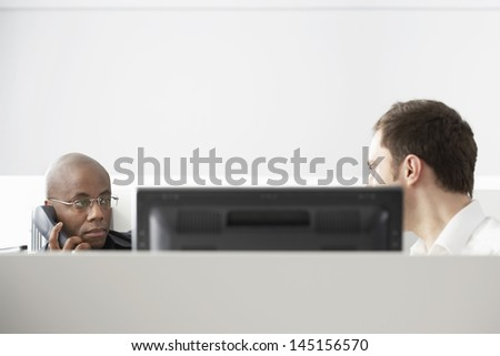 Two office workers sitting in office cubicle one using phone - stock photo