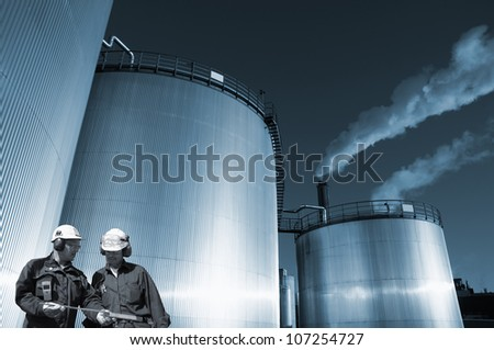 two oil and gas workers, large fuel storage tanks in background, blue toning concept