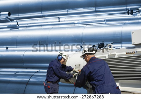 two oil workers with machinery, gas-pipes and pipelines in the background - stock photo