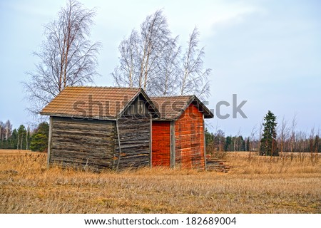 Two old barns by harvested field in rural Finland at spring, HDR effect - stock photo