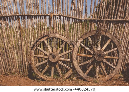 Two old  cart wheels as a symbol of fortune and fate near the wooden fence, filtered with soft pastel colors with filters. - stock photo