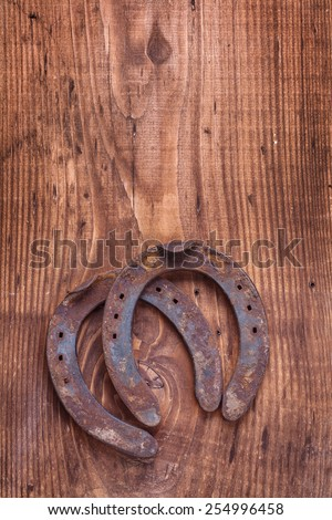 two old cast iron metal western horse shoeing accessory horseshoes on antique wooden board with copyspace  happy concept   - stock photo