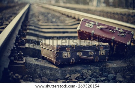Two old fashioned forgotten a suitcases lie on railroad tracks - stock photo