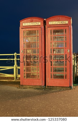 Two old-fashioned telephone boxes along the seashore in Brighton, England. - stock photo