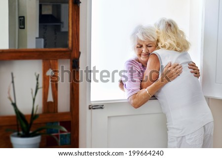 Two old friends hugging each other at the door after a great visit - stock photo