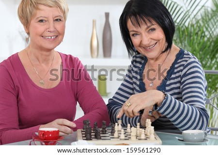 Two old friends playing chess - stock photo