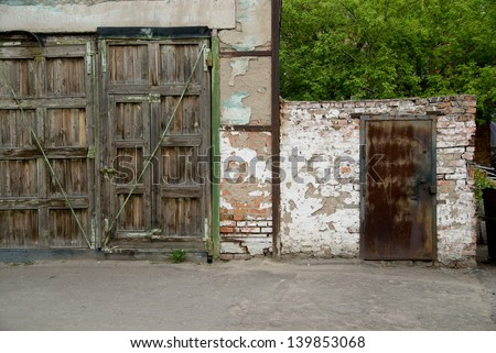 Two old garage door on the background of trees. - stock photo