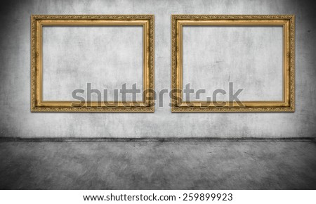 Two old golden frames on gray wall