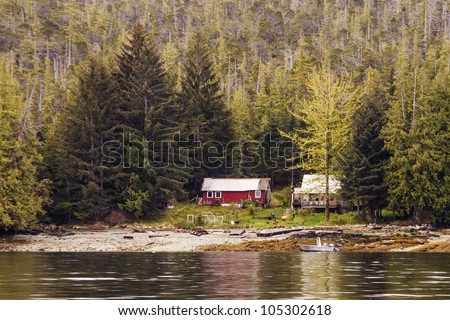 Two old houses on the coast of an Alaskan waterway surrounded by massive evergreens - stock photo