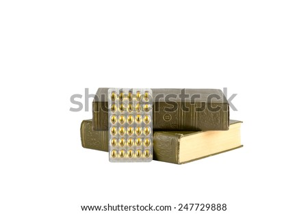 Two old medical books and new medicine pills in blister pack are isolated on white background