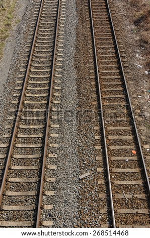 two old parallel railway tracks going into distance with two colored gravel and stones in between - stock photo