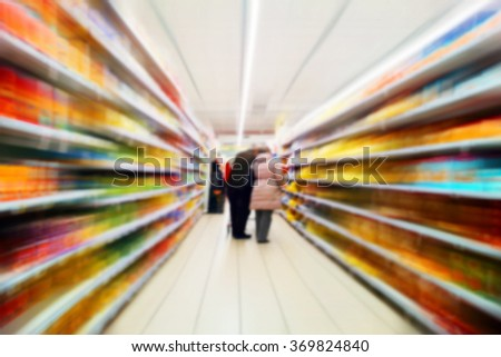 Two old person shopping in the supermarket, motion blur