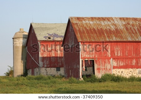 two old red barns with concrete silo - stock photo