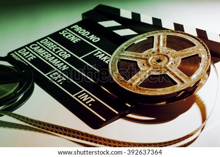 Two old reels of film and cinema clap lying on a light table. Toned image - stock photo