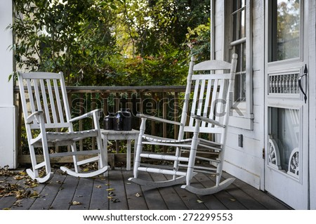 Two Old Rocking Chairs On The Front Porch Of An House