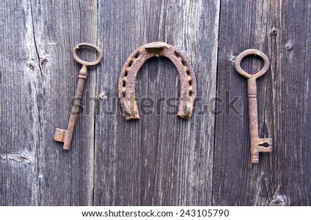 two old rusty historical key and luck symbol horseshoe on wooden farm wall - stock photo