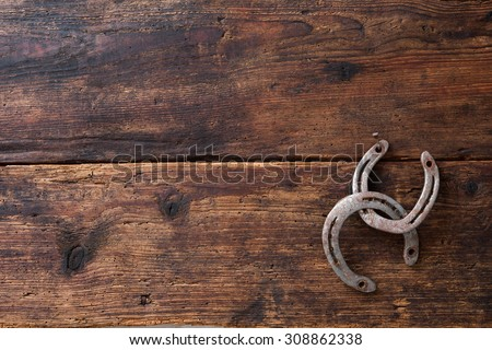 Two old rusty horseshoes on vintage wooden board - stock photo