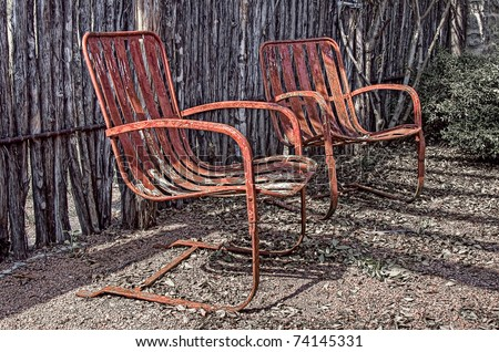 two old rusty red chairs next to a rustic fence - stock photo