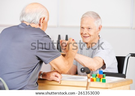Two old senior men holding hands for congratulation in a nursing home - stock photo