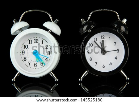 Two old style alarm clocks isolated on black