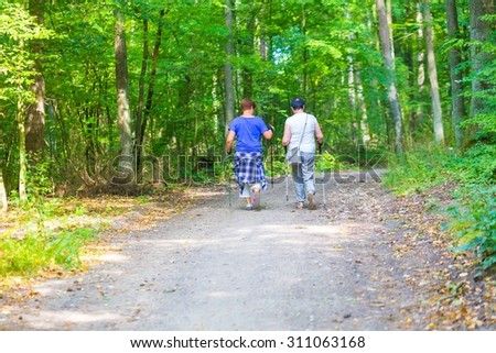 Two old womans nordic walking through forest path. Summertime forest with two ladies walking.