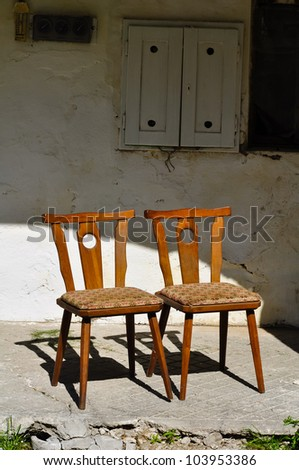 two old wooden chairs are standing close on an old porch