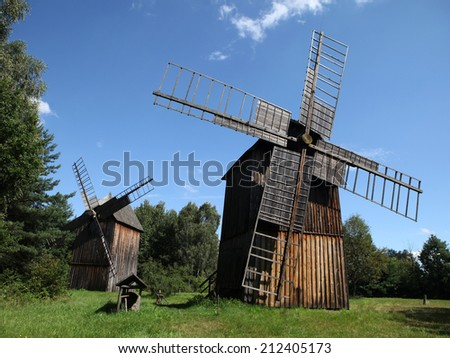 Two old wooden windmills against blue sky