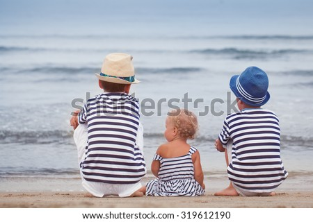 Two older brothers and little cute sister sit on beach and look at  sea, italy,  - stock photo